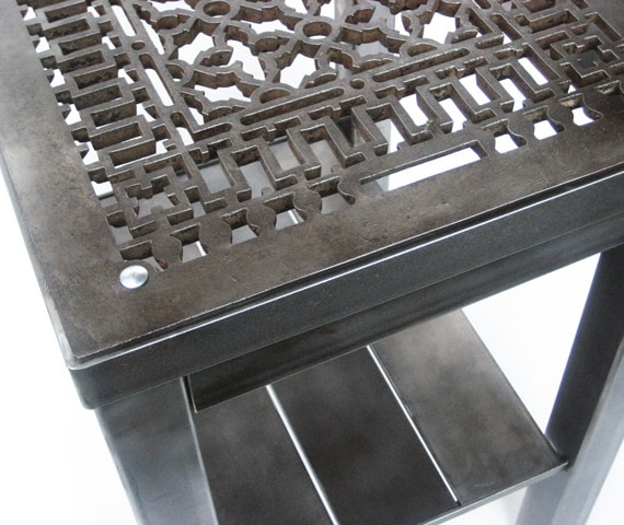 steel end table with intricate design cutouts