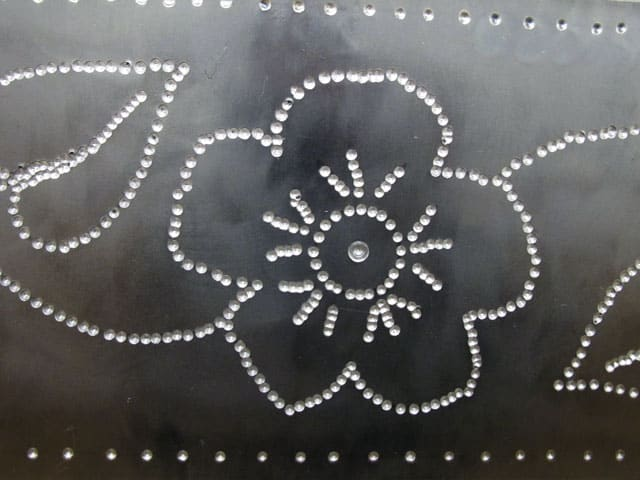 steel mirror with punched in flower detail